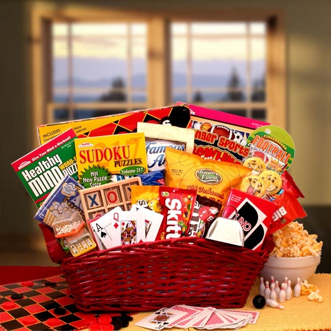 Large red wicker basket is filled with a Checkers game set, Word search puzzle, book, Sudoku puzzle book, Crossword puzzle book, Tic-tac-toe wooden game set, Word Boggle game cube, Finger bowling game, Mini travel game, Cowbell noise maker, UNO card game,Casino-style playing cards and a variety of snack and sweets