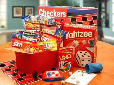Red gift box is filled with Playing cards, Checkers, a hand held travel size activity game and a variety of snacks and sweets for family fun!  Large size includes Yahtzee game and more snacks.