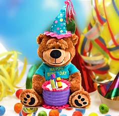 Adorable sitting brown plush bear wears a blue party hat and shirt and holds a fabric cake with candles. Sings the Happy Birthday song.